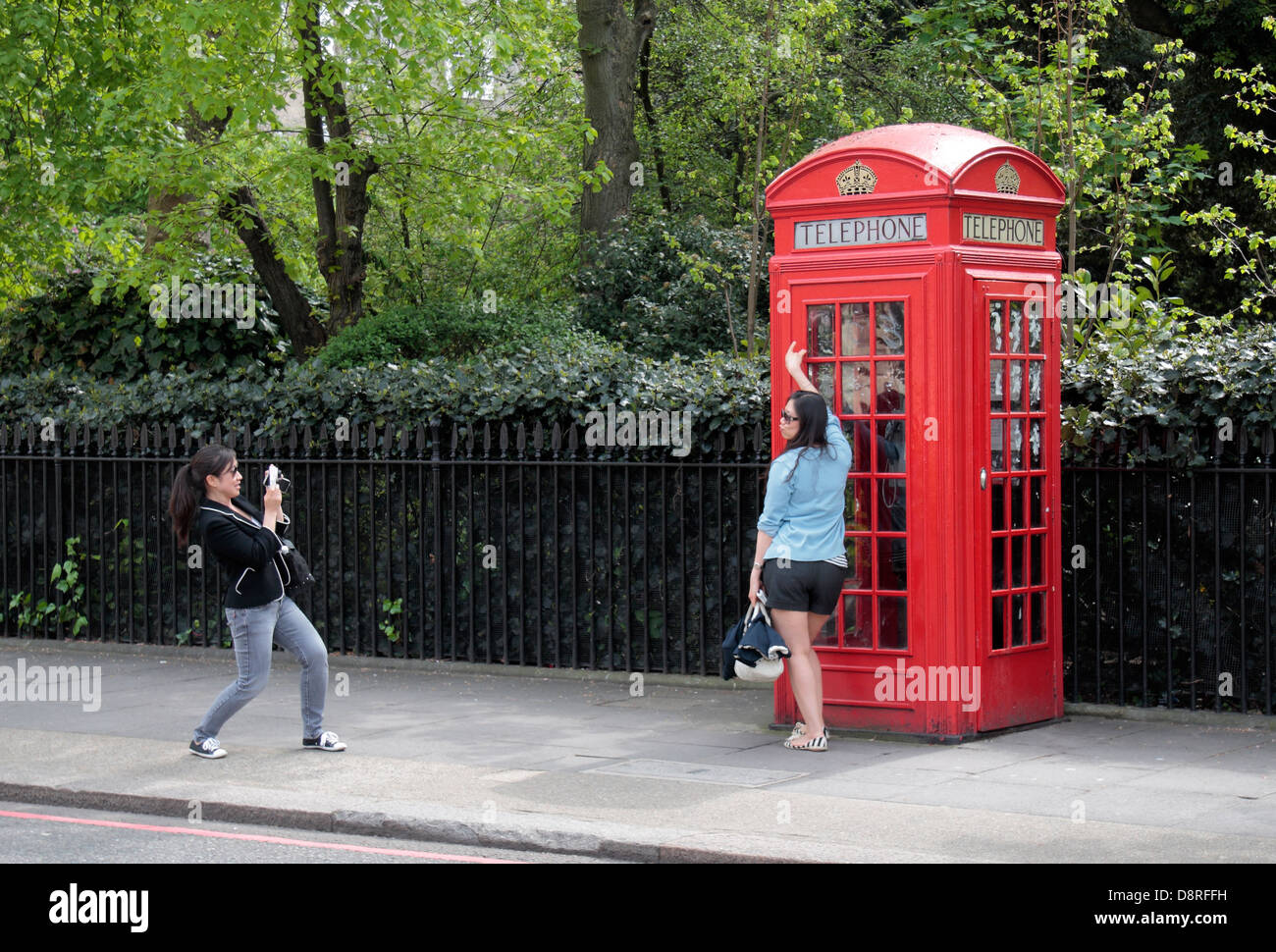 A tourist poses for her friend in front of an iconic symbol of Britain, a red telephone box in London, UK. - Stock Image