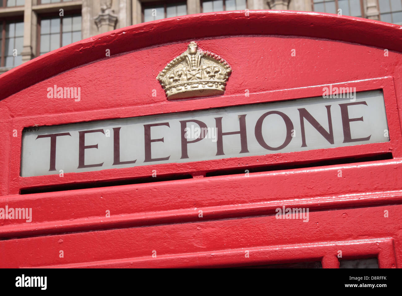 The top section showing he Royal Crown on the iconic red telephone box in London, UK. - Stock Image
