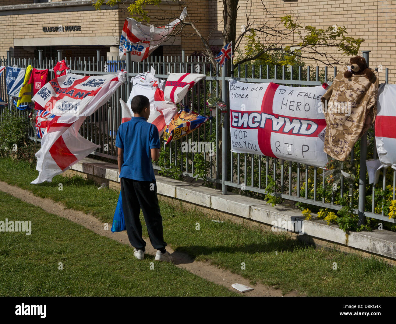 Child stands by floral tributes to Drummer Lee Rigby, killed outside Woolwich Barracks in London on May 22 - Stock Image