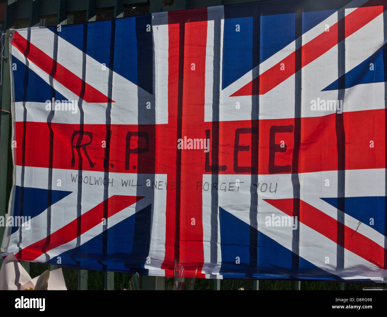 Union Jack flag and floral tributes to Drummer Lee Rigby, killed outside Woolwich Barracks in London on May 22  - Stock Image
