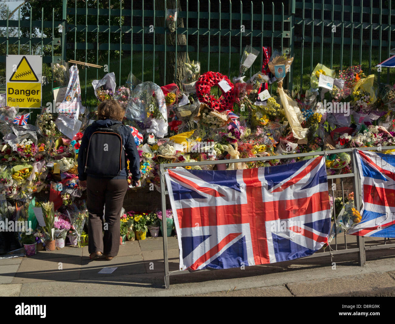 Woman watches floral tributes to Drummer Lee Rigby, killed outside Woolwich Barracks in London on May 22  - Stock Image
