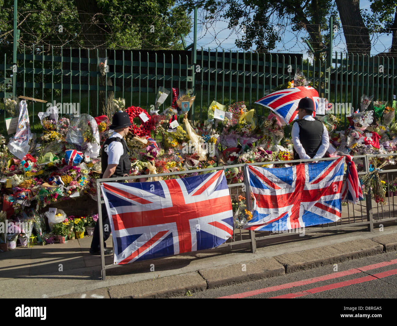 Police watch floral tributes to Drummer Lee Rigby, killed outside Woolwich Barracks in London on May 22 - Stock Image