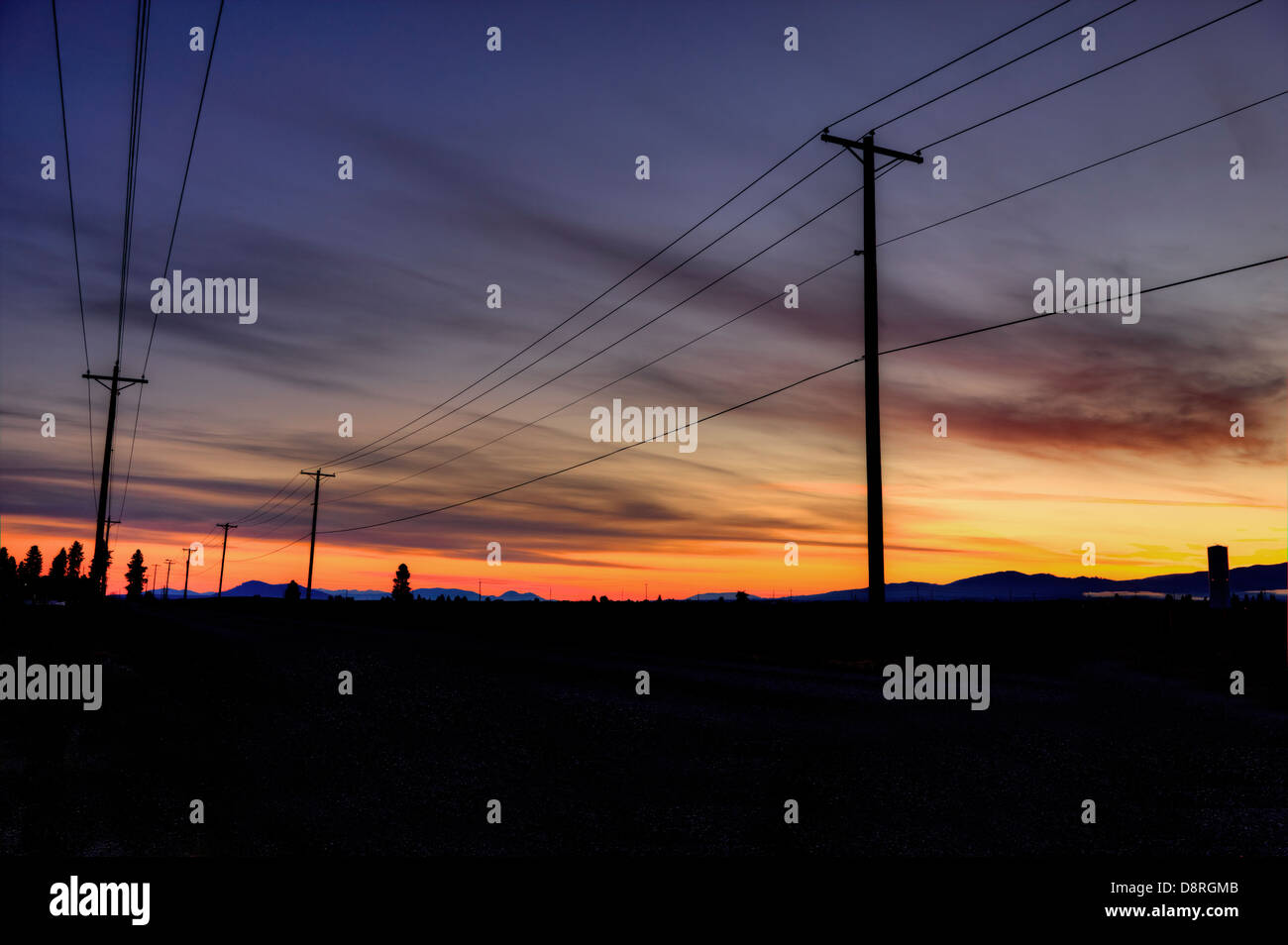 Power lines and poles are silhouetted against the sunrise sky. - Stock Image