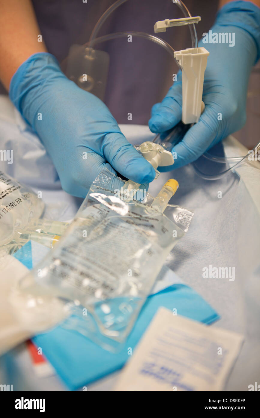 A nurse preparing a saline drip in a hospital. - Stock Image