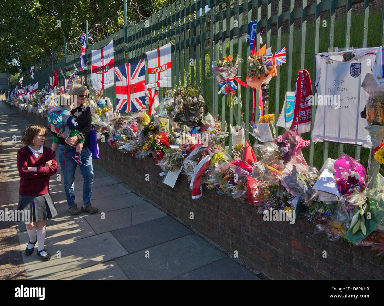 Mother and children walk past floral tributes to Drummer Lee Rigby, killed outside Woolwich Barracks in London on - Stock Image