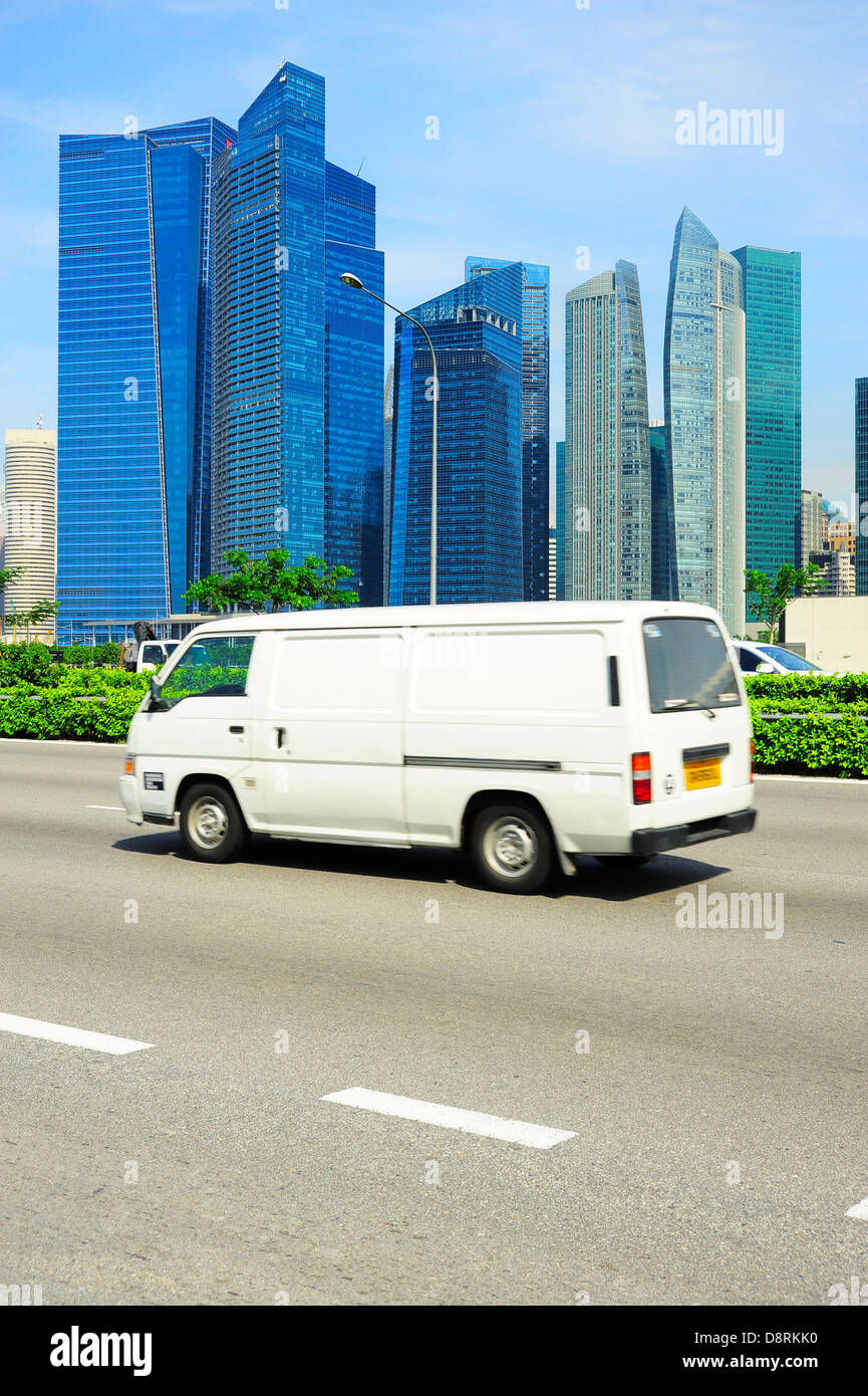 White minibus on the road in Singapore. Blurred motion - Stock Image