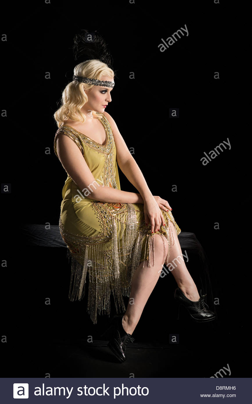 bd86abd47f0 Woman in a 1920 s flapper style beaded dress sitting on with a black  background.