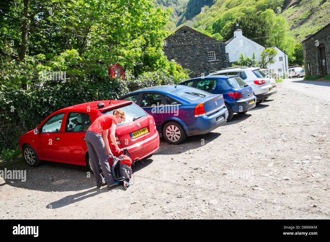 A female hiker returning to a parked car at Stonethwaite in the Lake District - Stock Image