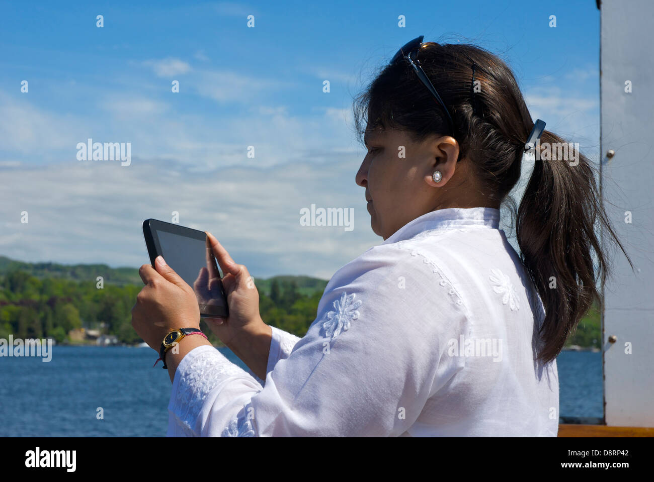 Asian lady on Windermere passenger boat, taking pictures on a tablet computer, Lake District National Park, Cumbria, - Stock Image