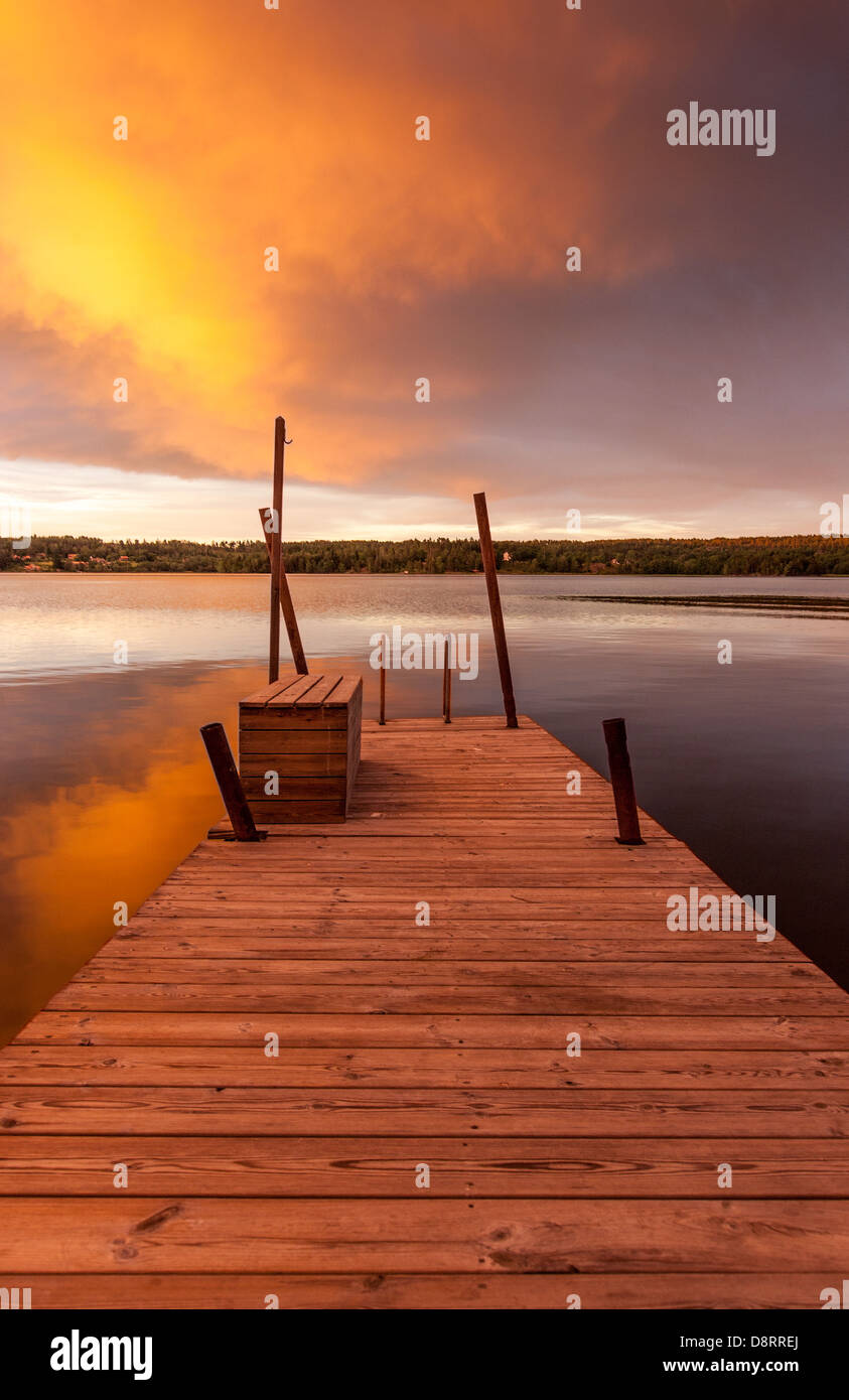 A view along a wooden jetty across a lake at dusk, vivid orange and blue sky, Sweden - Stock Image