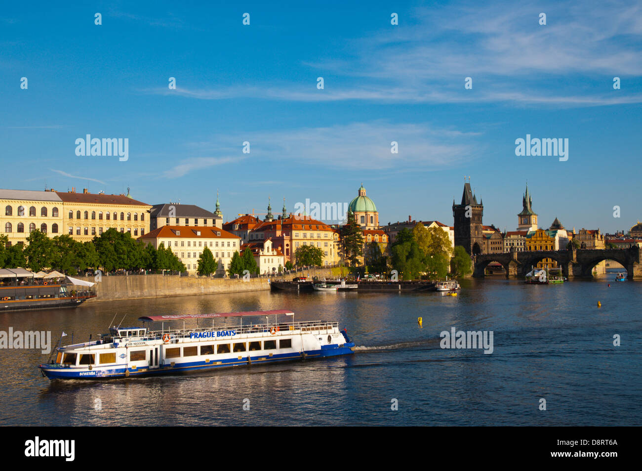 Tourist sightseeing boat on river Vltava with Charles Bridge and old town in background Prague city Czech Republic - Stock Image