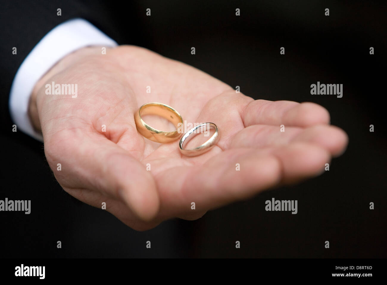 Two gold wedding rings held in the open palm of a man\'s hand showing ...