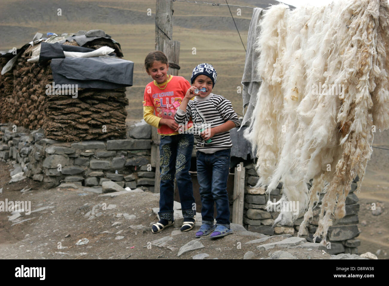 Local kids playing on the street of the shepherd mountain village of Xinaliq, Azerbaijan, Caucasus mountains - Stock Image