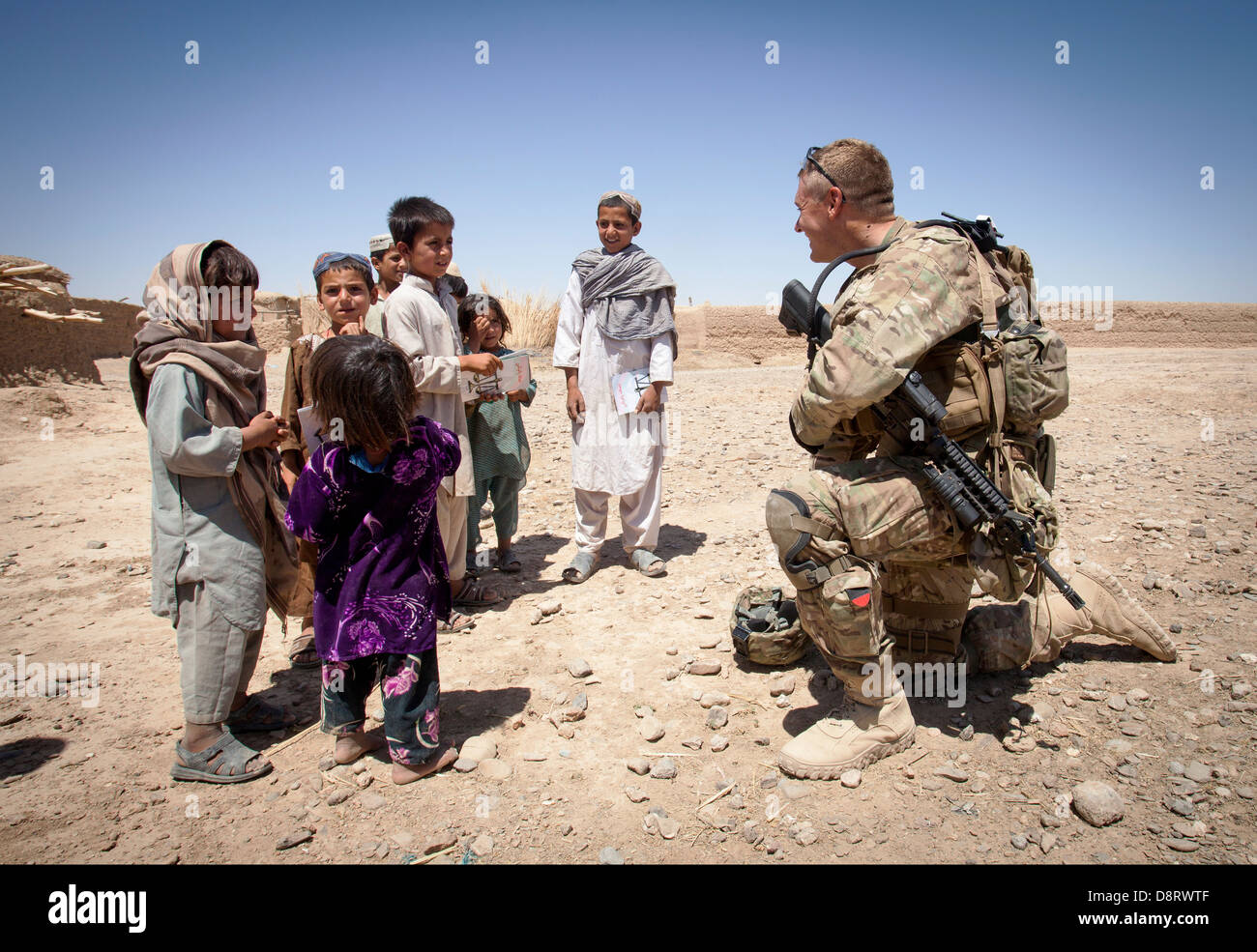 US Army Staff Sgt. Matthew Parsons with the Police Adviser Team Delaram talks with Afghan children May 26, 2013 - Stock Image