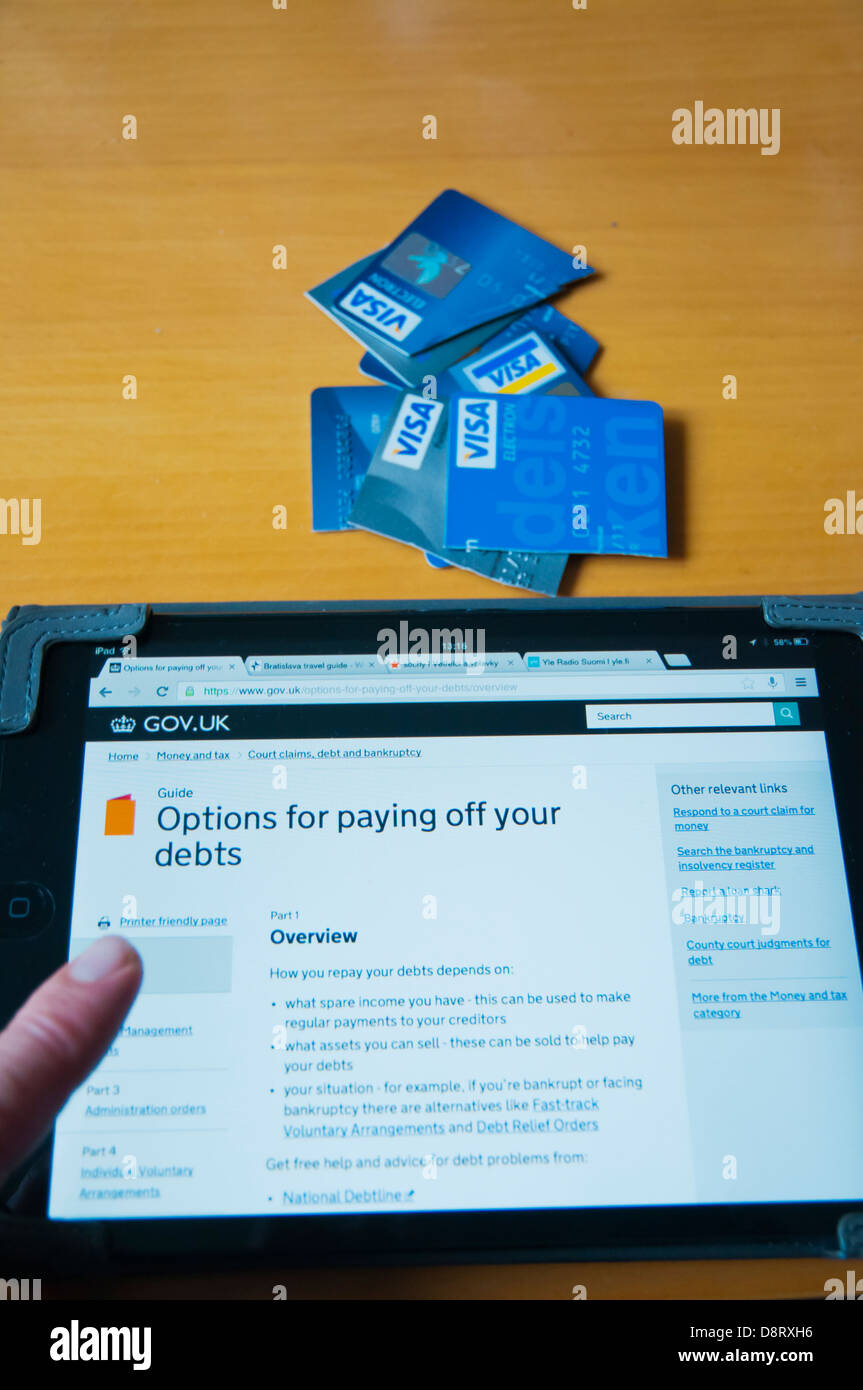 Person looking into UK debt relief information on internet on ipad mini tablet computer at home - Stock Image