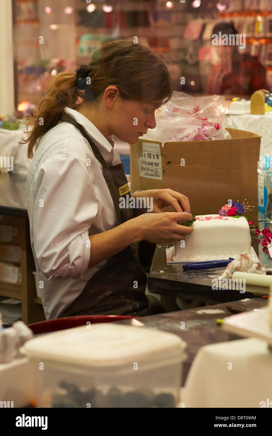 Looking through window of cake shop with young woman decorating iced cake at Oxford in May Stock Photo