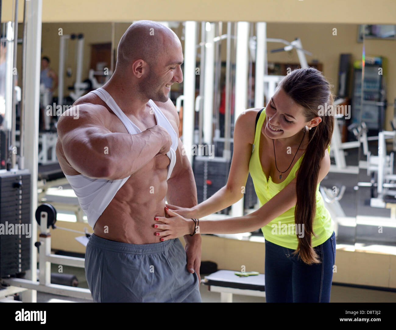 woman checks abdominal muscles athlete - Stock Image
