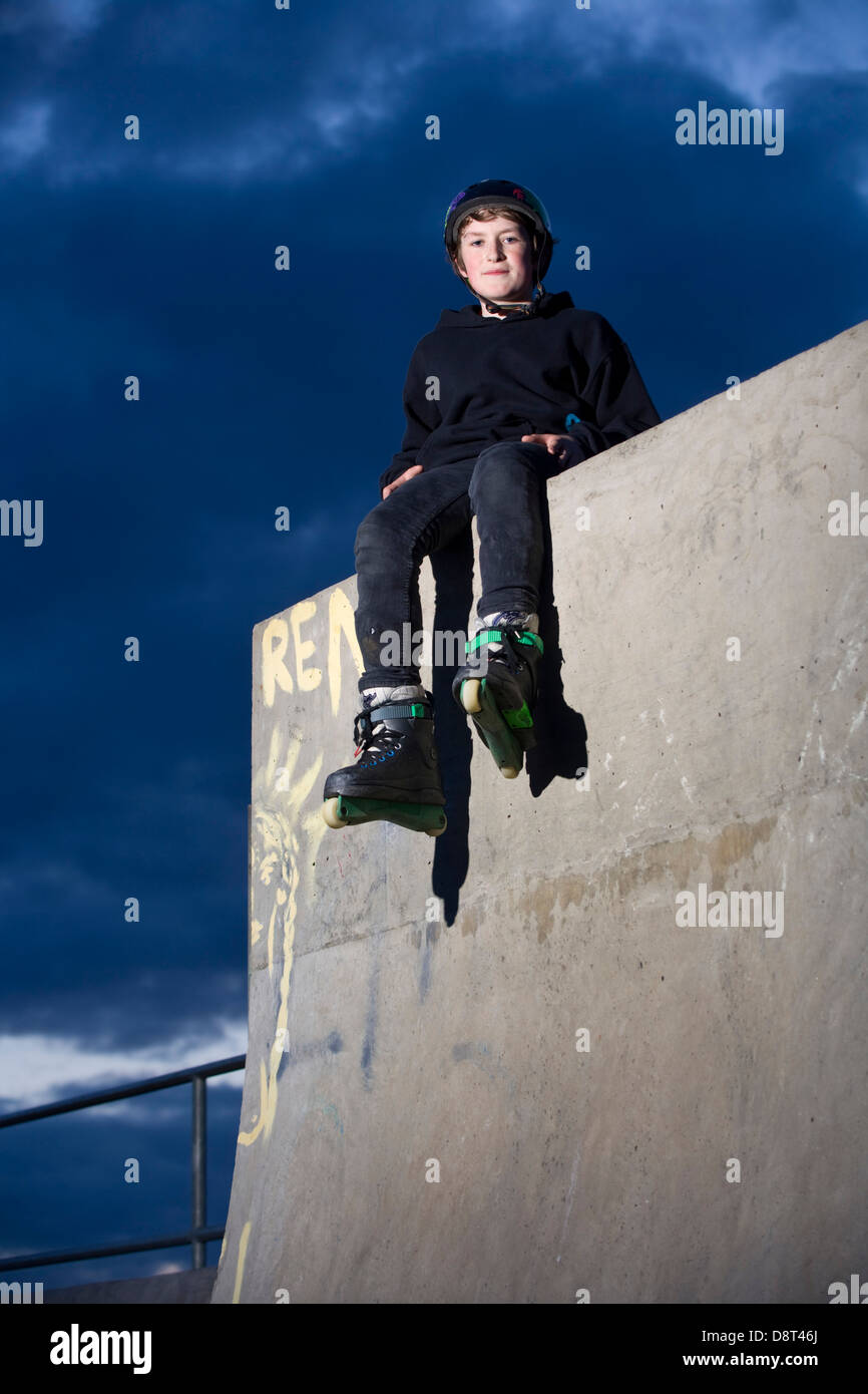 A young inline skater siting on top of a high concrete wall in a skate park. - Stock Image