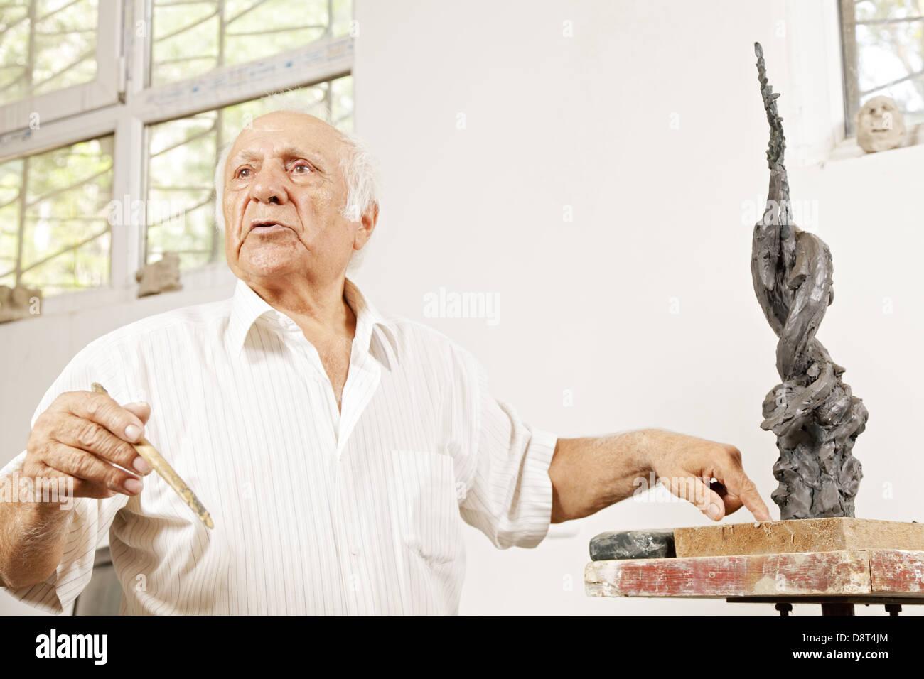 Senior sculptor describing his sculpture - Stock Image