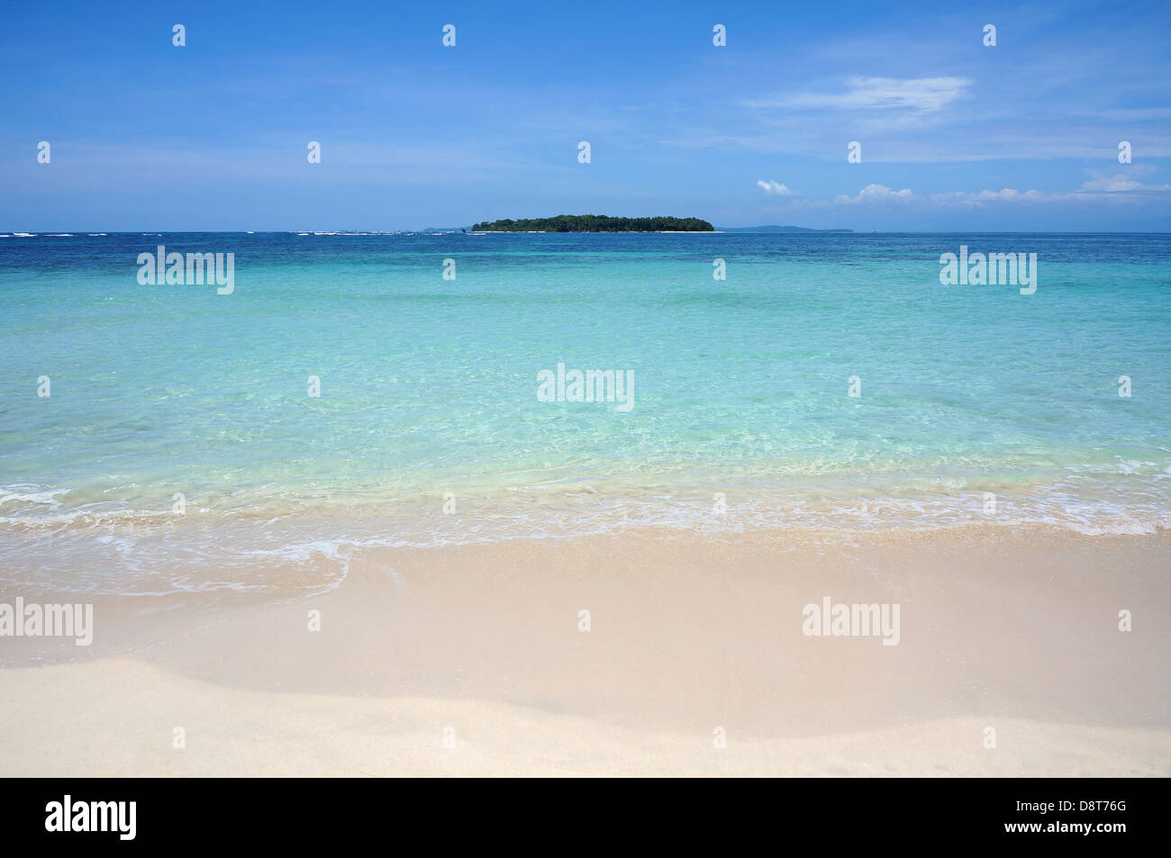 Tropical sandy beach shore with turquoise water and an island at the horizon, Caribbean sea - Stock Image