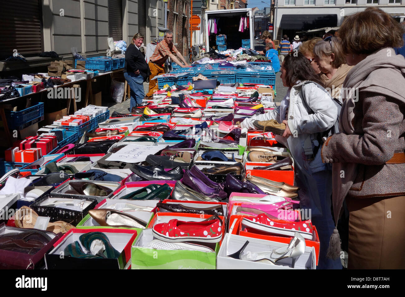 Women buying second hand shoes at flea market in town Stock Photo