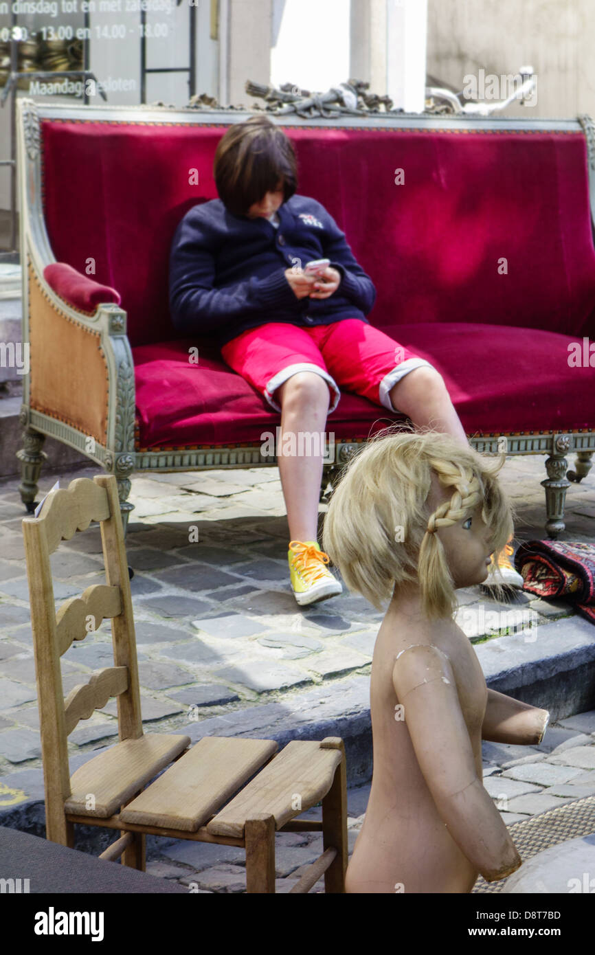 Bored child playing with smartphone sitting in antique couch at flea market - Stock Image
