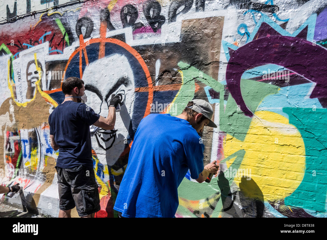 Youngsters with spray cans in alley spraying colourful graffiti on wall of building in town