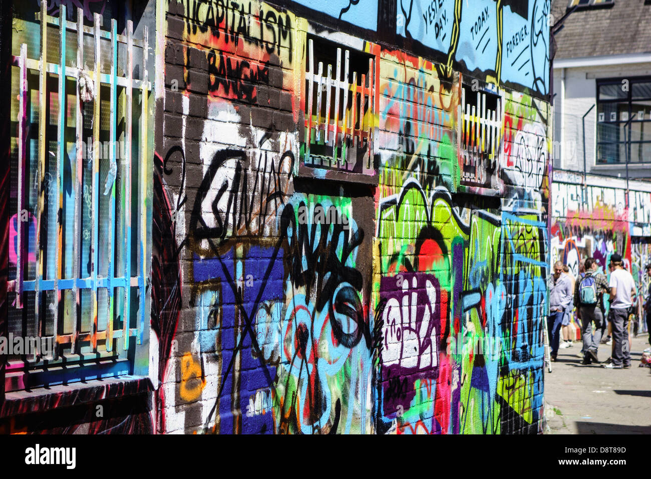 Youngsters in alley spraying colourful graffiti on wall of building in city Stock Photo