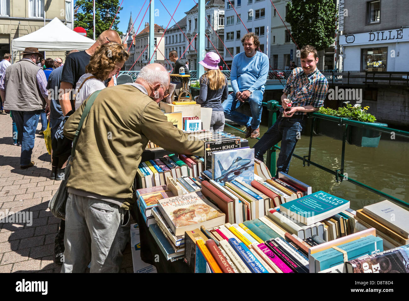 Elderly man buying secondhand used books at stand at the Ajuinlei book market in Ghent, Belgium - Stock Image
