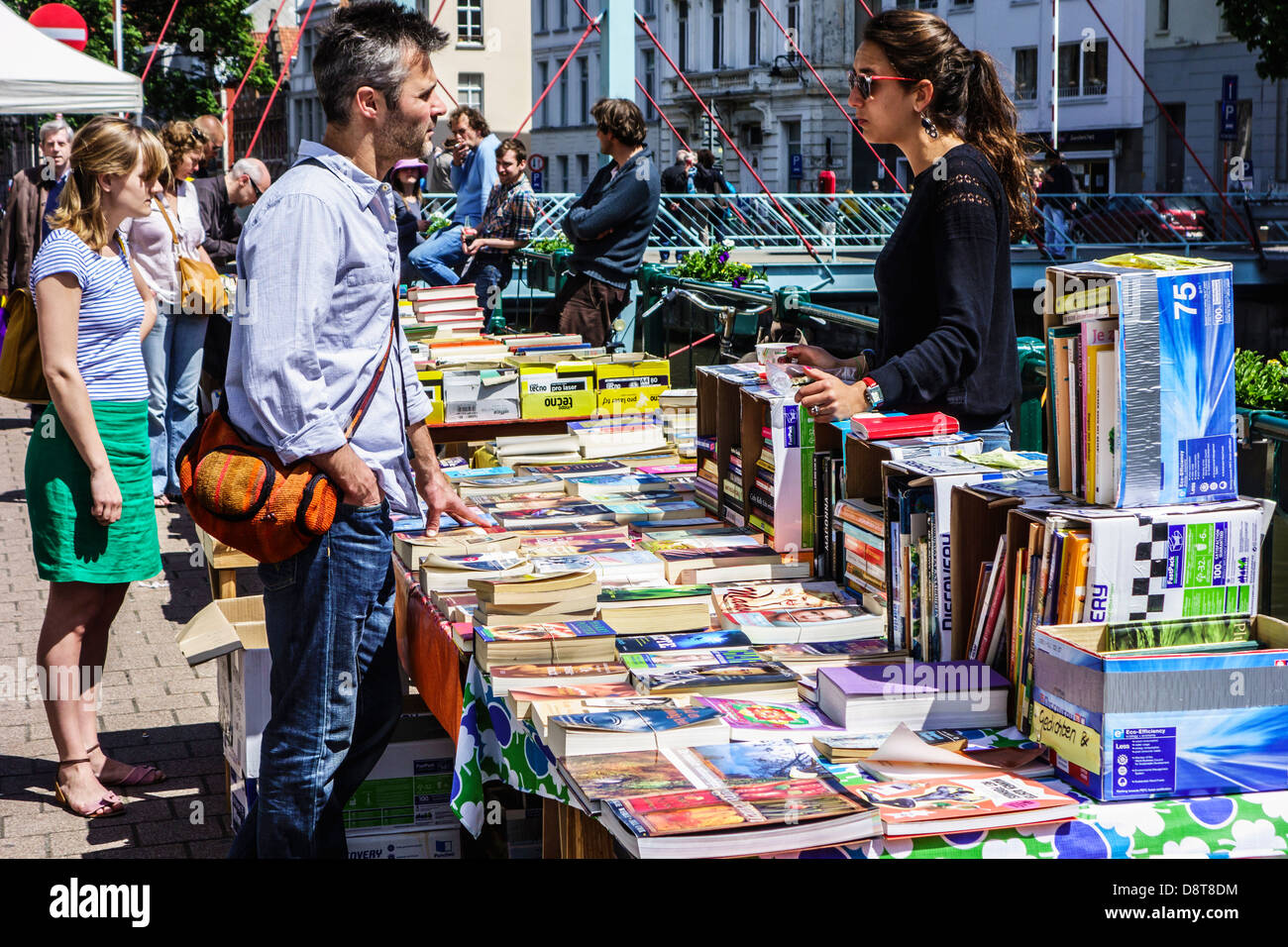 Man buying secondhand used books from stallholder at the Ajuinlei book market in Ghent, Belgium - Stock Image