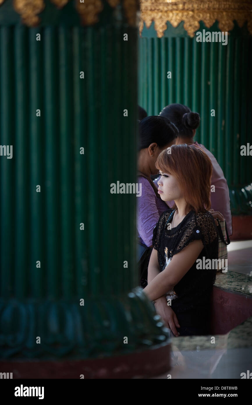 A young woman waits in the shade between green columns in the Schwedagon temple complex in Rangoon (Yangon) Burma - Stock Image