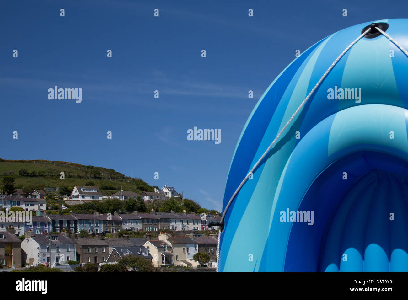 New Quay (Cei Newydd) beach and pastel painted terrace houses with inflatabe dingy - Stock Image