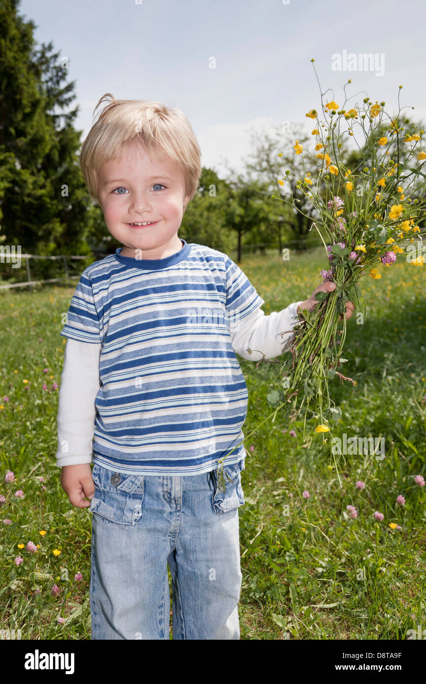 Three year-old boy with a bouquet of flowers - Stock Image