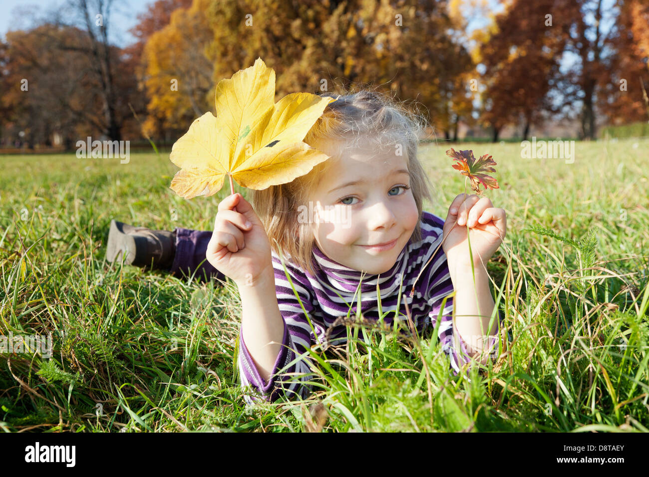 Six year-old girl with an autumn leave in one hand and a flower in the other hand - Stock Image