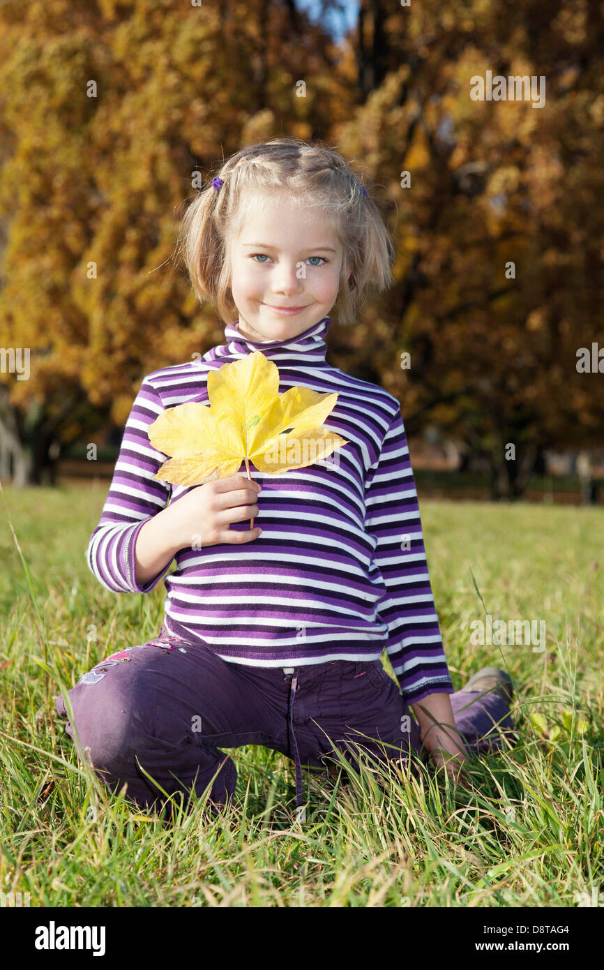 Six year-old girl with an autumn leave in the hand - Stock Image