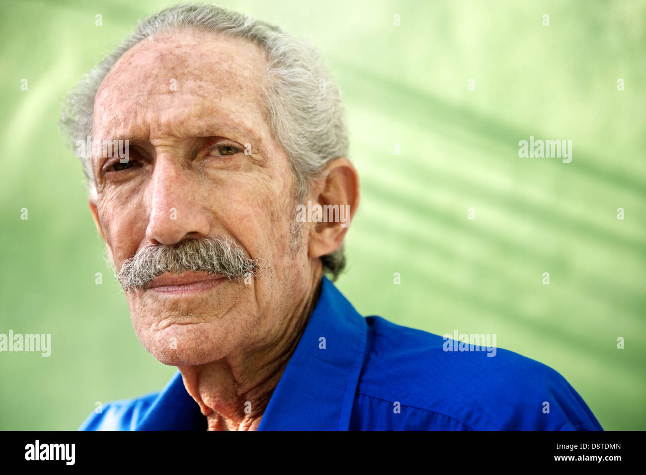 Elderly people and emotions, portrait of serious senior caucasian man looking at camera against green wall - Stock Image