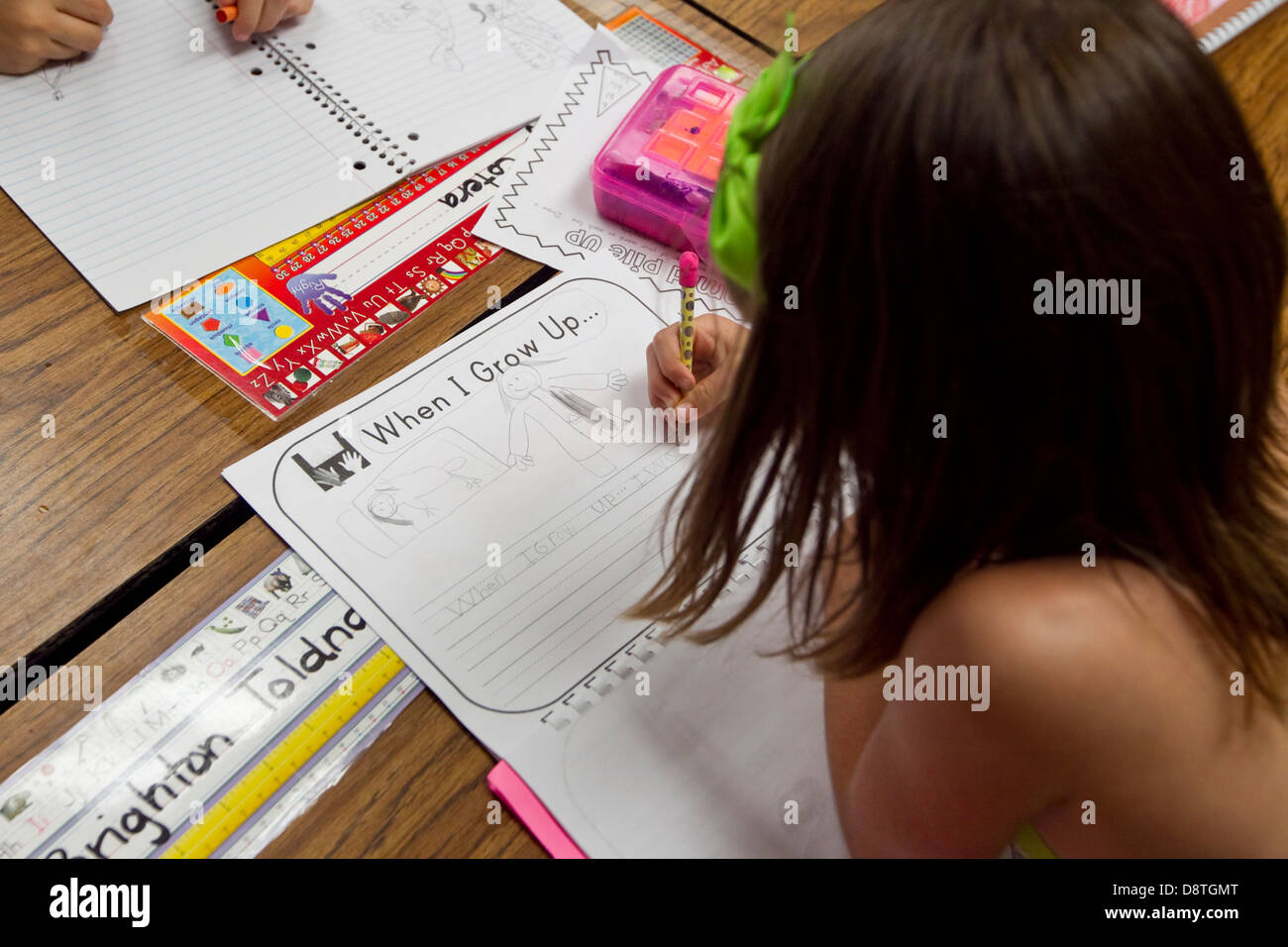 First Grade Elementary School Girl Student Write And Draws In Stock