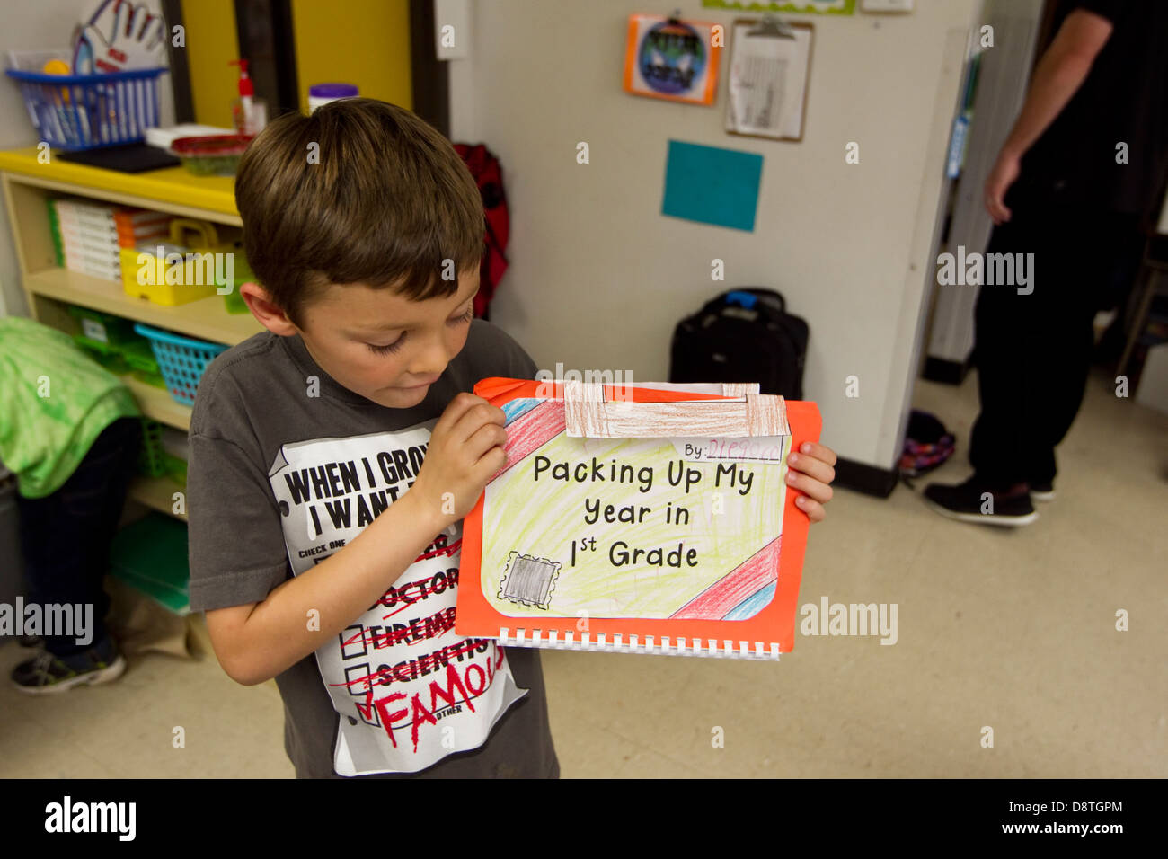First grade 7 year old boy hold up his end of year project in his elementary school classroom in Texas - Stock Image
