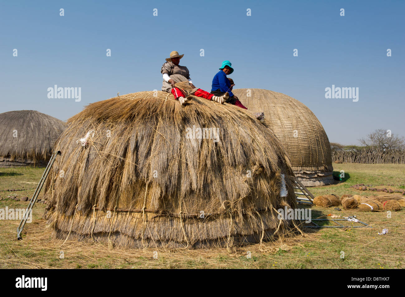 Woman thatching a hut at Ondini Heritage Site, Recreation of King Cetshwayo's residence at Ondini, Ulundi, South - Stock Image