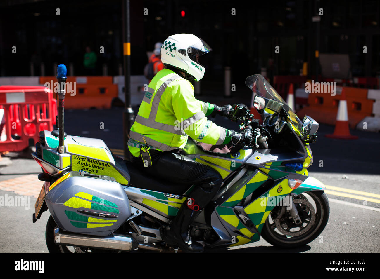 A West Midlands ambulance paramedic on motorcycle on the streets of Britain driving off left to right in full ambulance - Stock Image
