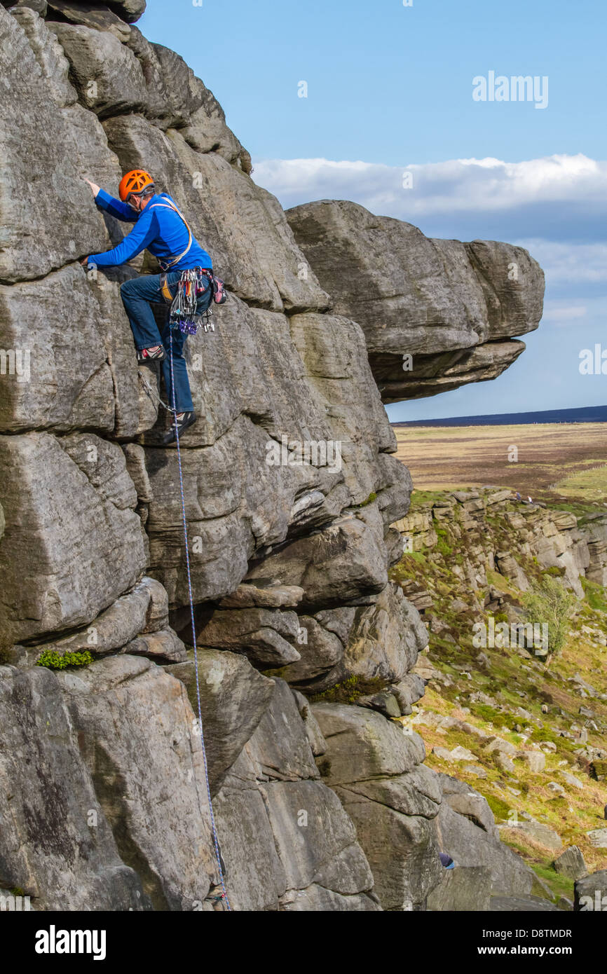 Traditional rock climber person climbing a rock climbing route at Stanage Edge, UK - Stock Image