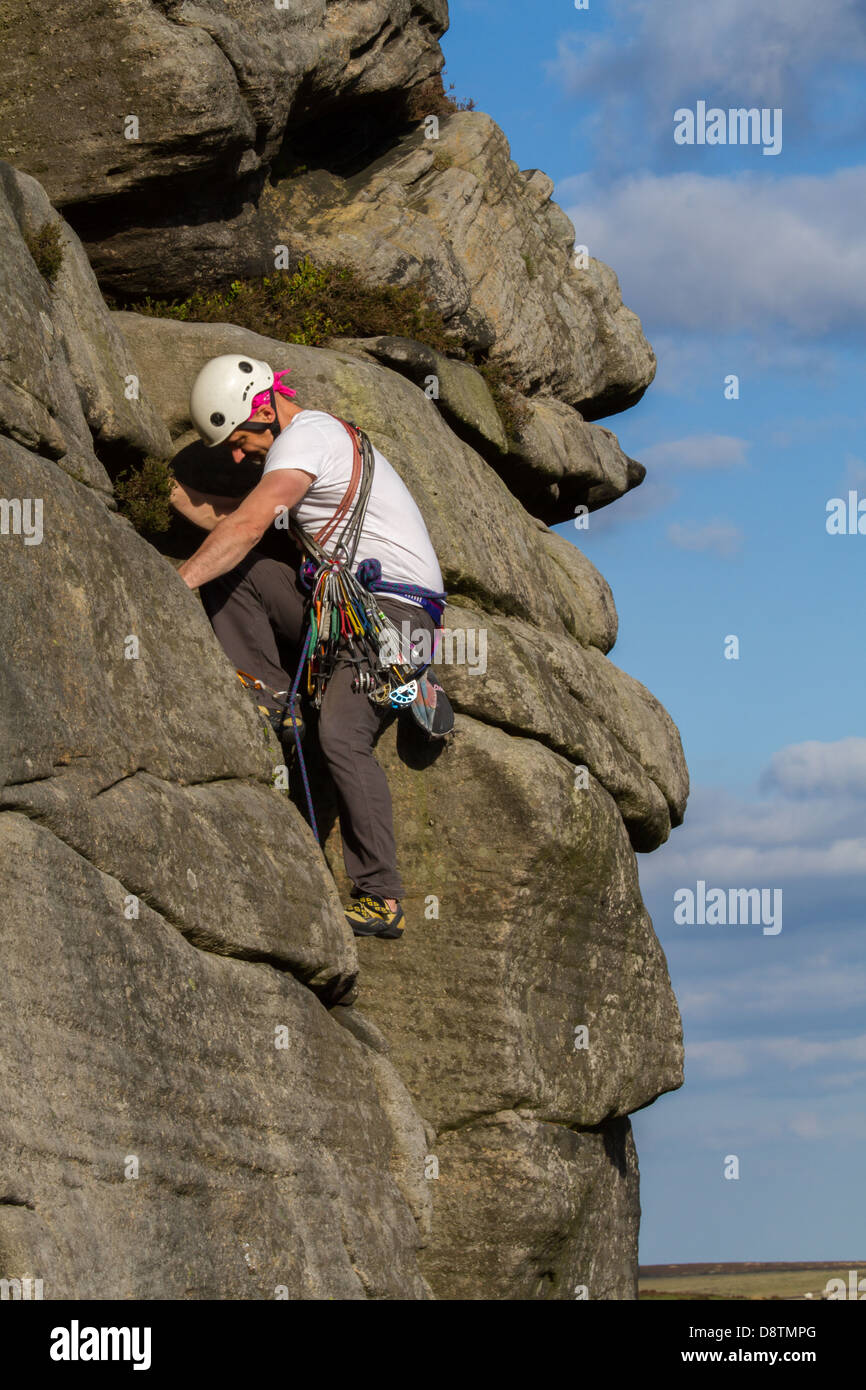 Traditional rock climber person climbing a rock climbing route at Stanage Edge - Stock Image