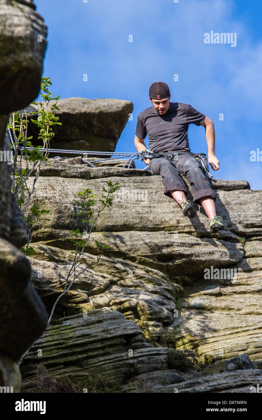 Rock climber person belaying against blue sky at Stanage Edge - Stock Image