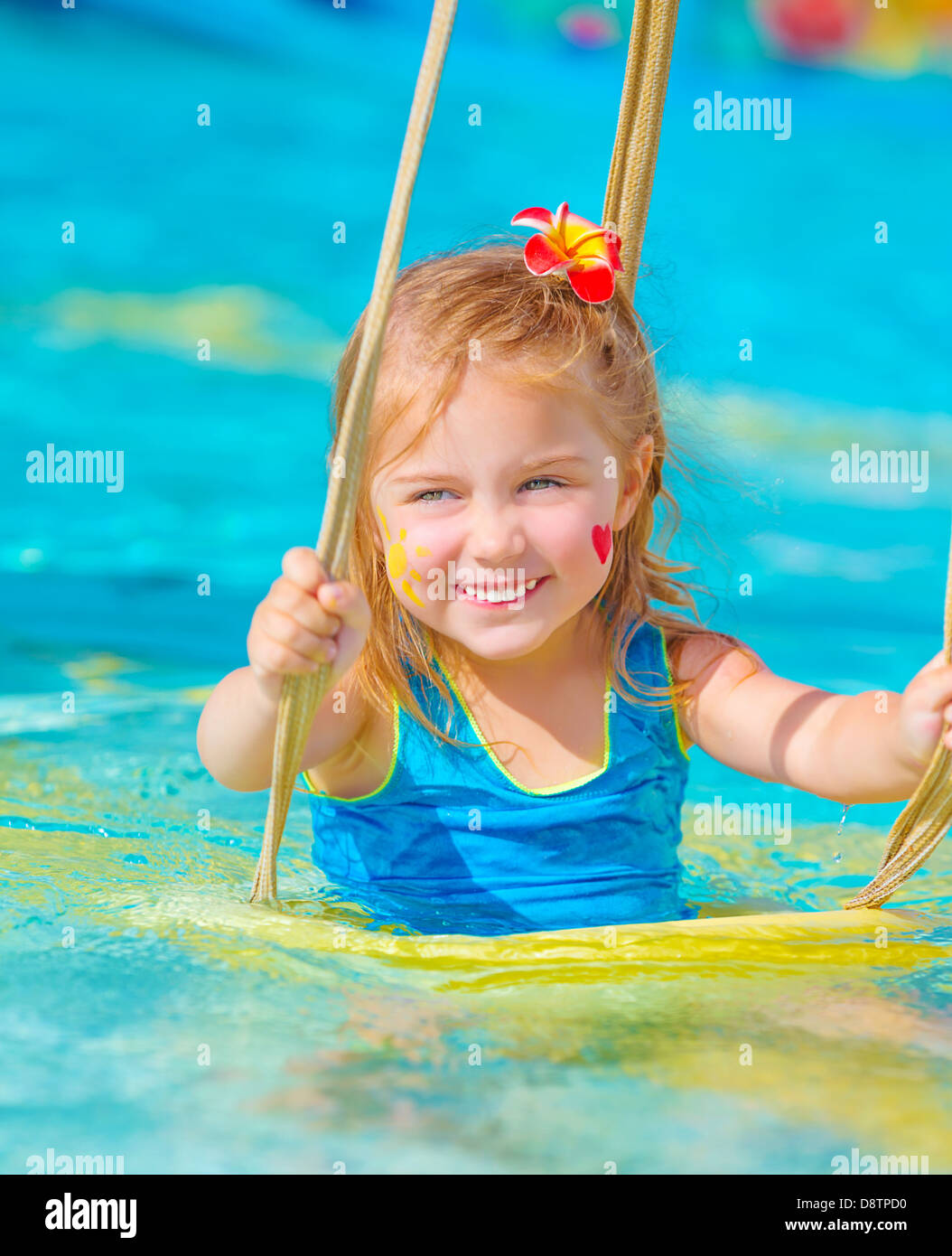 Cute happy girl enjoying summer holiday in the pool, having fun on water swing, red frangipani flower in hair, red - Stock Image