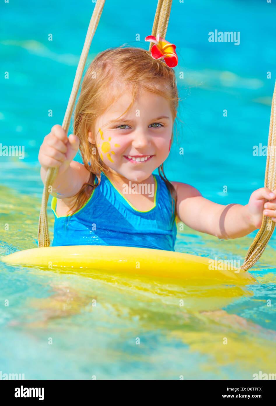 Cute happy baby girl enjoying summer holiday in the pool ...
