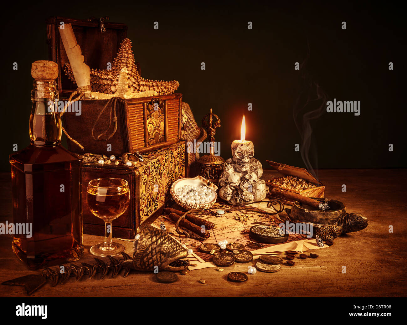 Closeup on treasure still life, luxury vintage accessories, pirates booty, bottle with rum, fish skeleton, cigars - Stock Image