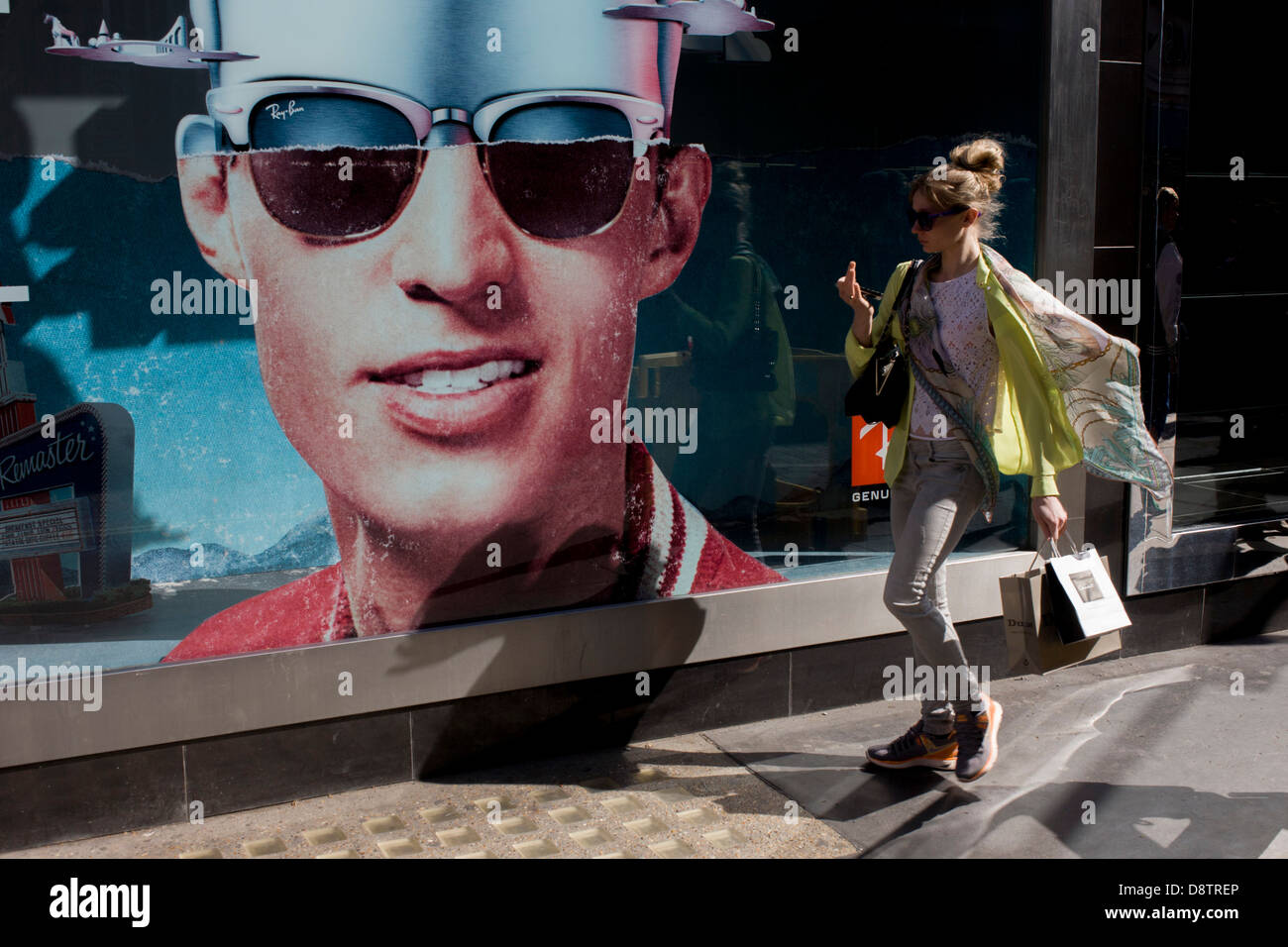 0eecf237c2 A trendy young woman passes-by a poster of a model showing stylish shades  outside