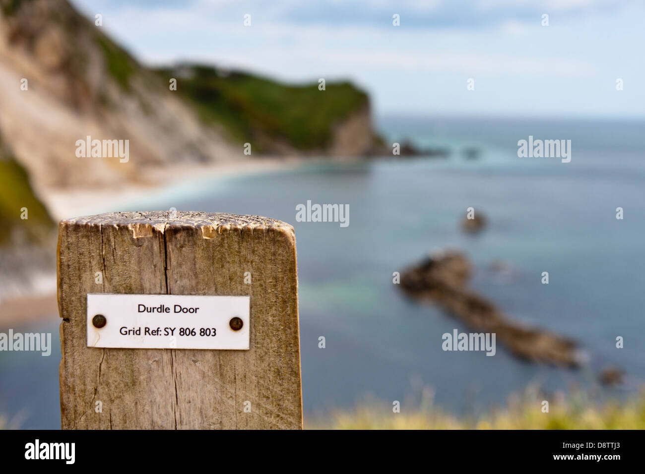 Grid reference on fence post giving map location for walkers at Durdle Door in Dorset. Out of focus background. - Stock Image