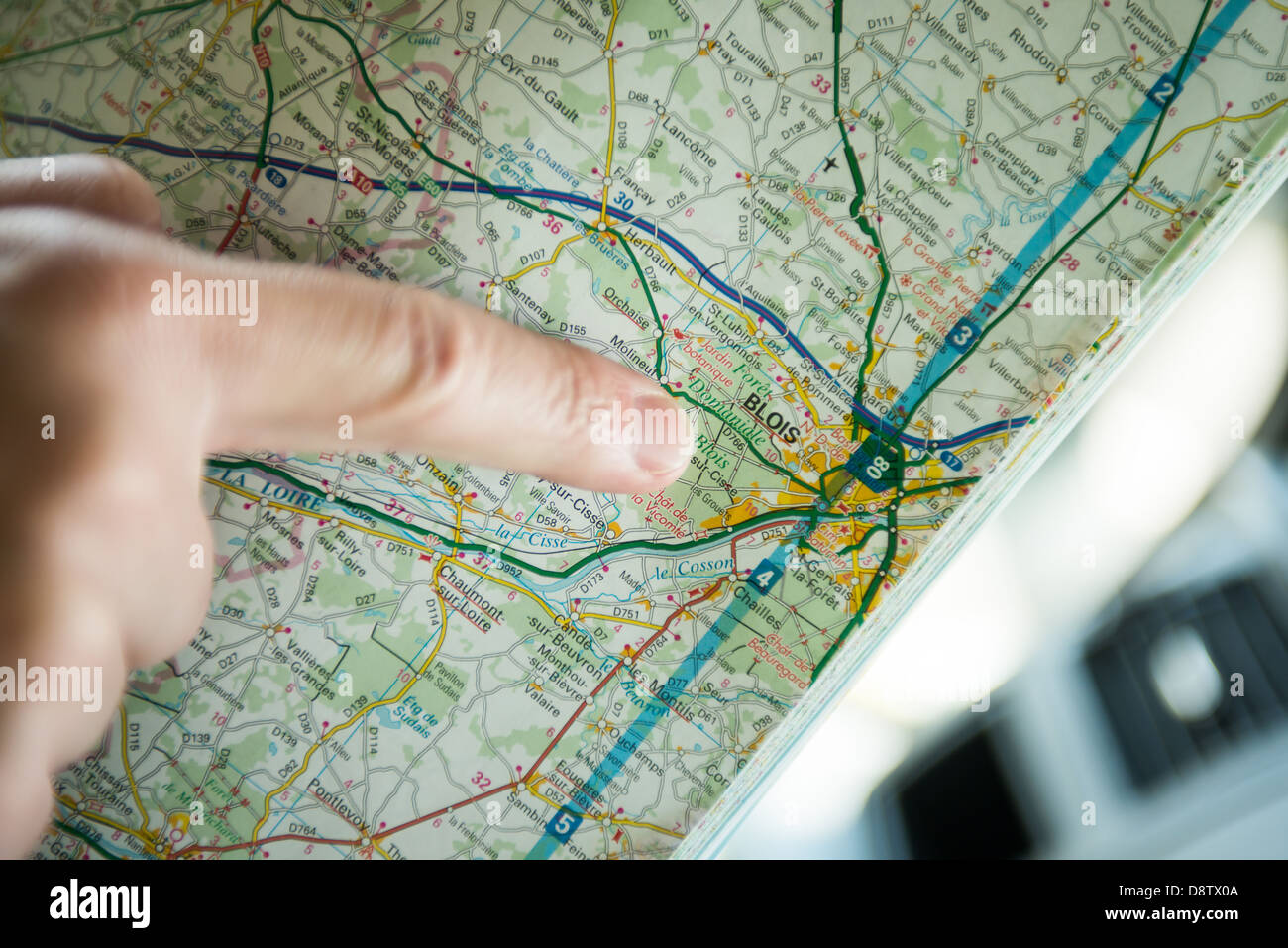 A finger pointing at Blois, France on a map - Stock Image