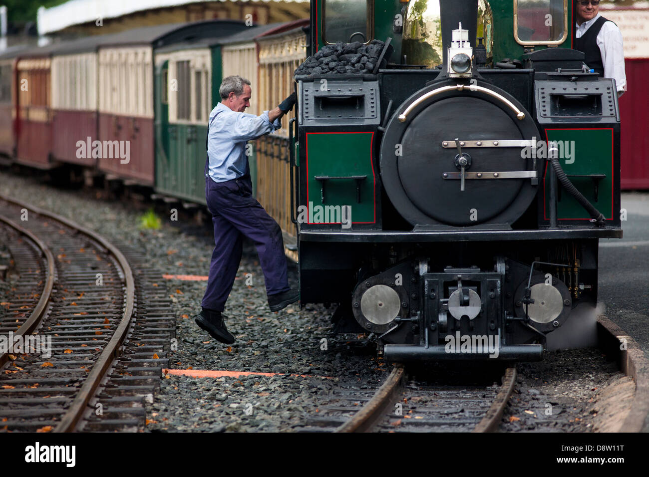 The fireman climbs onto the steam engine of Ffestiniog Railway, a historical steam railway operated from Wales - Stock Image